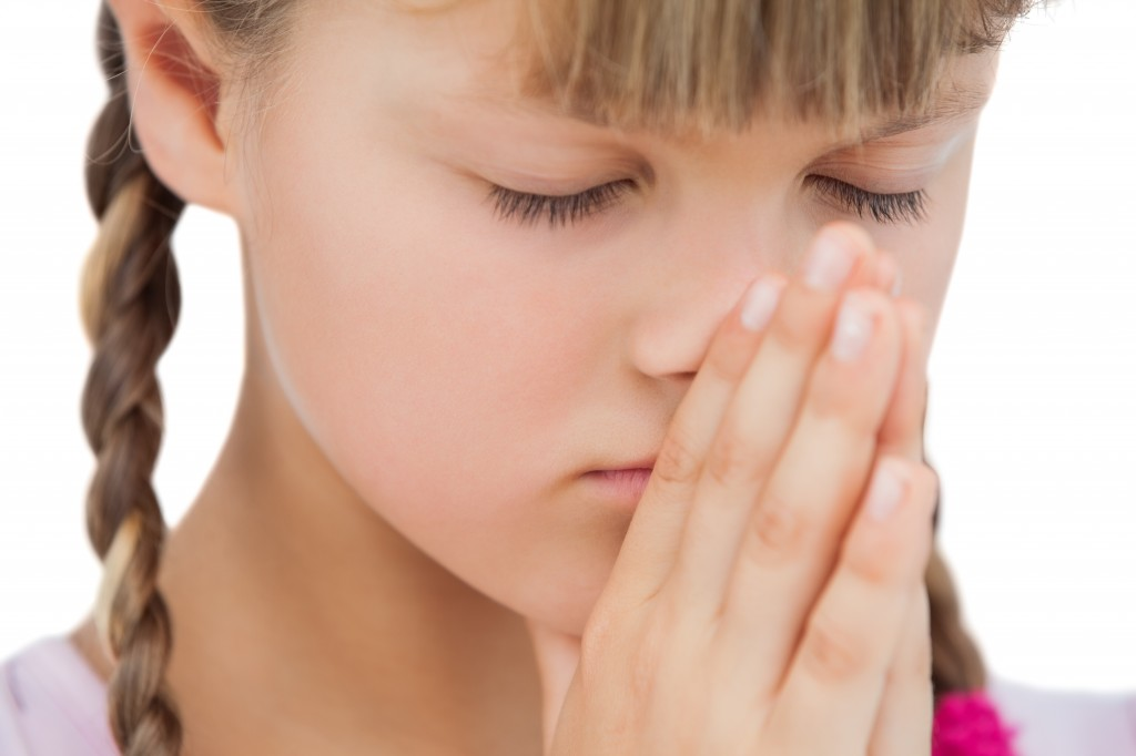 Little blonde girl praying on white background