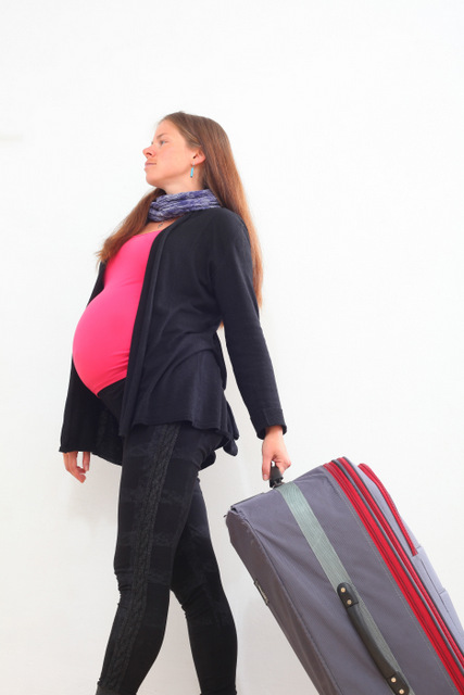 Pregnant woman with a suitcase and a bag is going to vacation