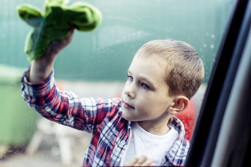child car washes. boy in a plaid shirt carefully cleans the car window. soft focus