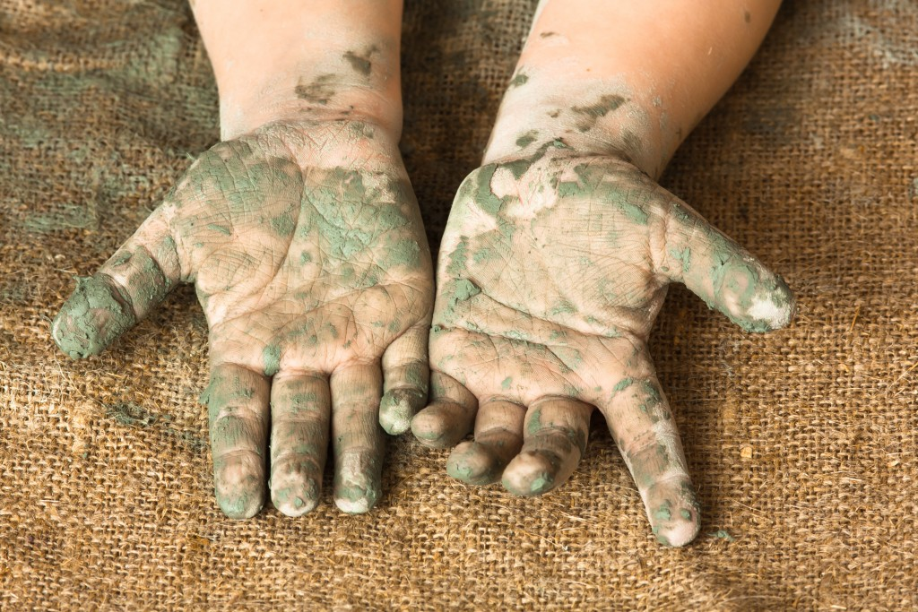 hands of child after working with blue clay, closeup