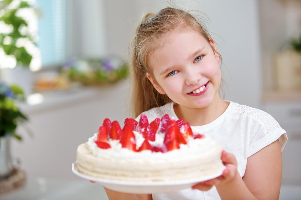 Glückliches Kind hält eine Erdbeertorte mit frischen Erdbeeren in beiden Händen