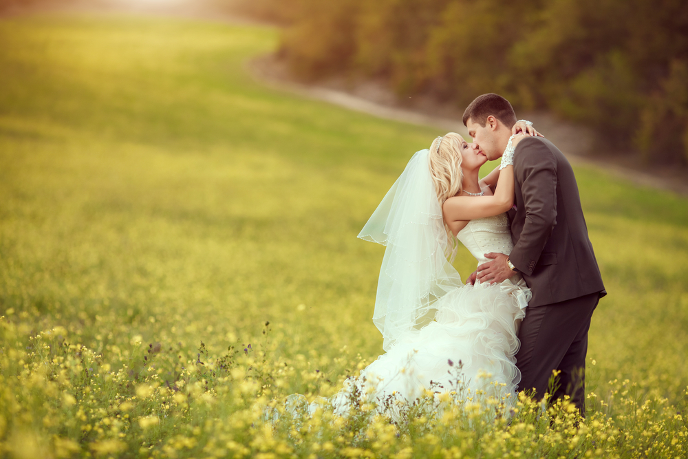 spring-wedding-couple-kissing-field-flowers